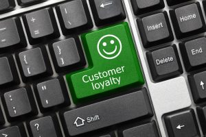 Close-up view on conceptual keyboard - Customer loyalty (green key)